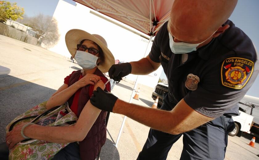 Yuyao Lui, 76, receives a COVID-19 vaccine shot.