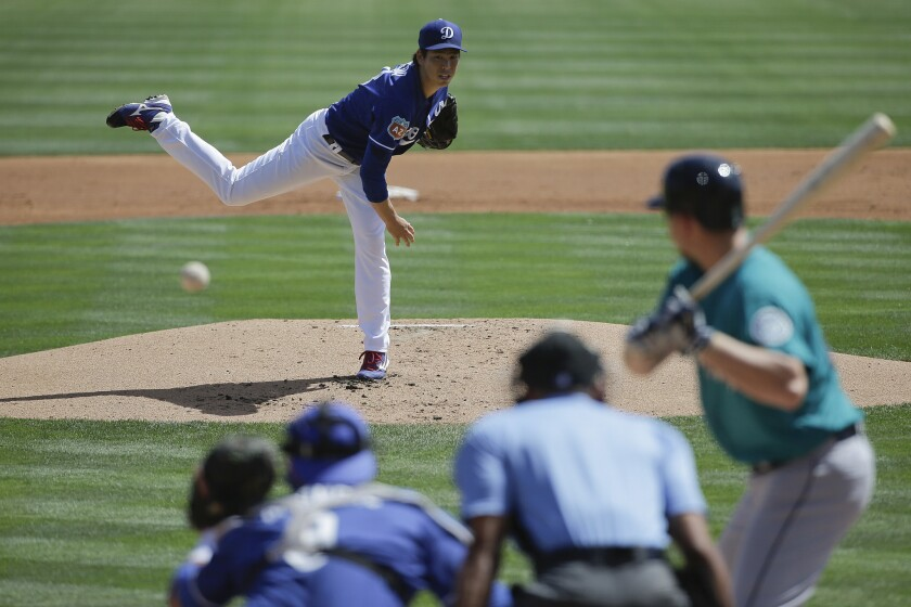 Dodgers starting pitcher Kenta Maeda throws against the Mariners during the first inning of a spring training game.