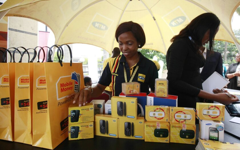 FILE- In this Monday April. 22, 2013 file photo, staff of MTN Nigeria work during the launch of mobile number portability in Lagos, Nigeria. Nigerian authorities have renewed the operating license of the MTN telecommunications group as the company faces a multi-billion dollar fine for failing to co