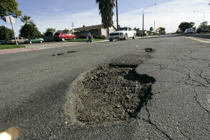 January 05,  2011,- San Diego  CA,-After the recent series of storms the city has been left pockmarked with potholes.  City crews from the streets division are out in force trying to get as many filled as they can.  On northbound Sandrock Road south of Aero Drive several deep holes force alert driv