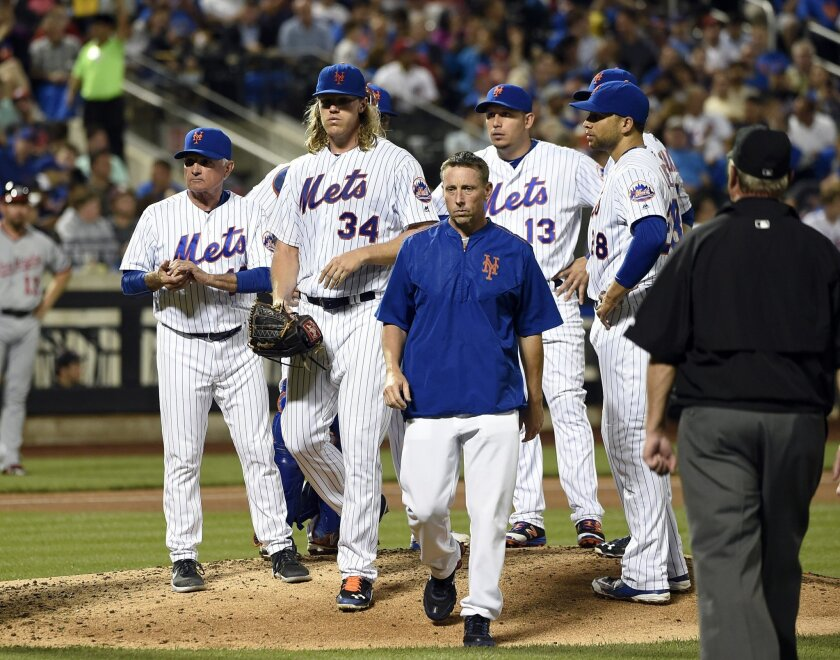 New York Mets manager Terry Collins, left, looks to the dugout as a trainer escorts starting pitcher Noah Syndergaard (34) from the mound in the fifth inning of a baseball game against the Washington Nationals, Friday, July 8, 2016, in New York. (AP Photo/Kathy Kmonicek)