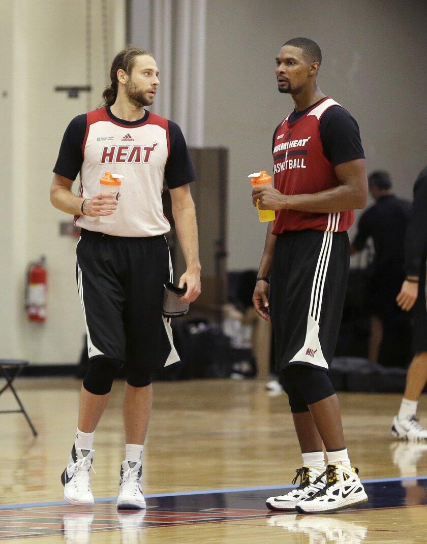 Miami Heat forward Josh McRoberts, left, and Chris Bosh talk during during a break at NBA basketball training camp, Tuesday, Sept. 29, 2015, in Boca Raton, Fla. (AP Photo/Alan Diaz)