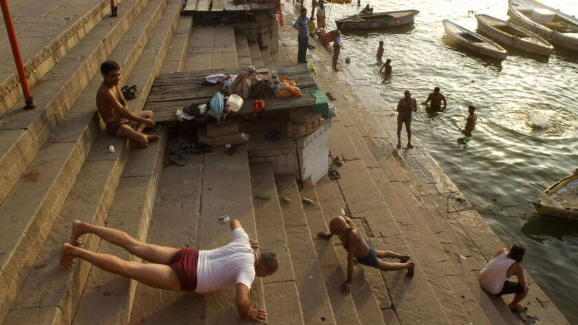 Two men perform morning exercises by the River Ganges in Varanasi, India, Tuesday, July 10, 2012. Va