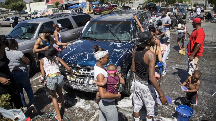 Hundreds of family and friends participate in a car wash to benefit the family of Travon Williams, 9, who was shot and killed outside Superior Liquor Store on July 8 in San Bernardino.