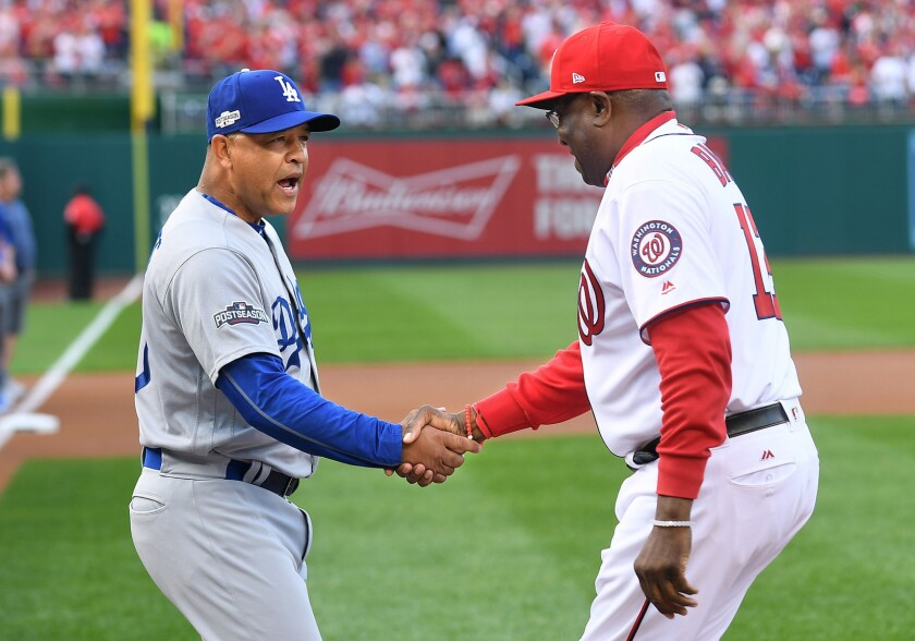 Dodgers Manager Dave Roberts and Nationals Manager Dusty Baker shake hands beforeGame 1 of the NLDS.