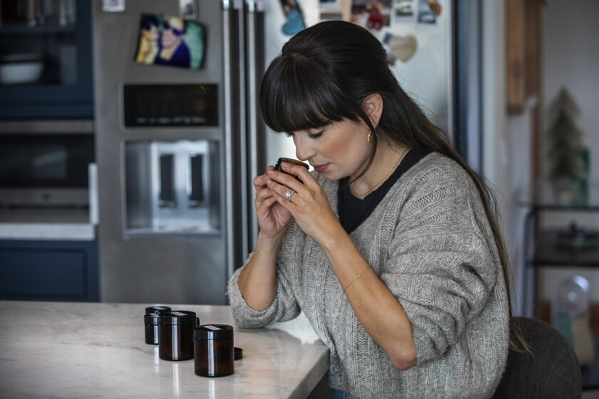 EAGLE ROCK, CA - DECEMBER 23, 2020: Mariana Castro-Salzman, 32, does smell training with essential oils at her home in Eagle Rock. Castro-Salzman lost her sense of smell after testing positive for COVID-19 back in March of 2020. To get it back, she is doing smell training, that consists of doing three rounds of smelling a variety of essential oils for 20 seconds each, twice a day. (Mel Melcon / Los Angeles Times)