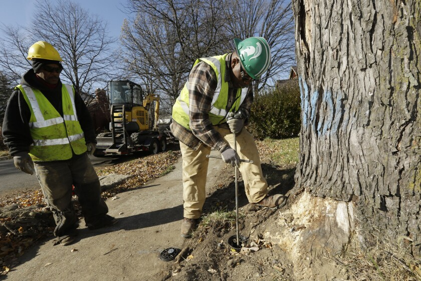 Detroit utility workers shut off the water to an abandoned home in Detroit.