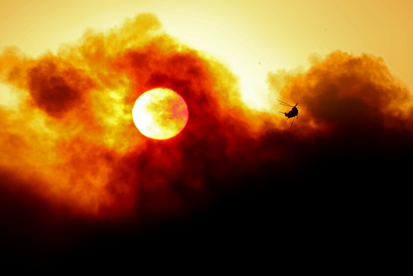 The sun is partially obscured by smoke as a firefighting helicopter prepares to make a water drop