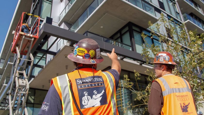 Superintendent Rocky La Rocco (left) works with Ben Park (right) at the Alexan apartment building at 14th and K Streets in downtown in mid-October.