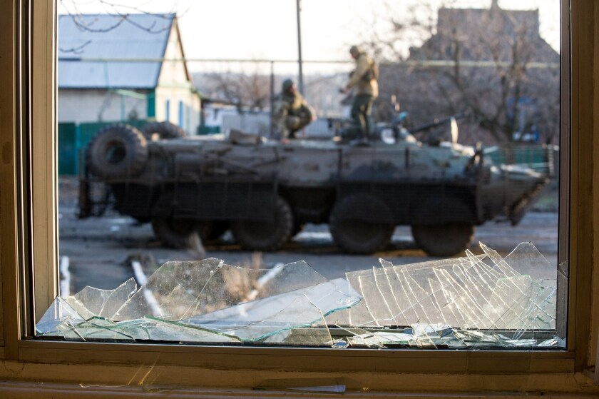 Ukrainian servicemen are seen standing on an Armoured Personnel Vehicle through a broken window in the Donetsk region.