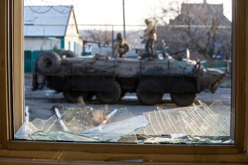 Ukrainian servicemen are seen standing on an Armoured Personnel Vehicle through a broken window in the Donetsk region.