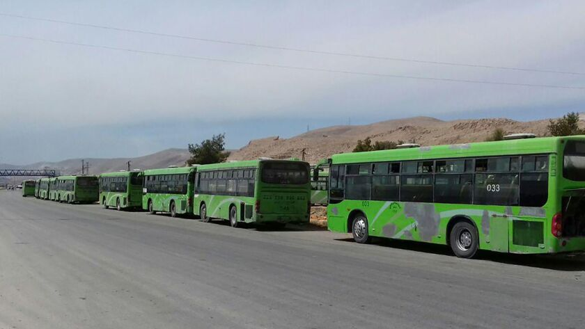 A picture released by the state-run Syrian Arab News Agency shows buses waiting to take members of the opposition evacuated from the rebel-held city of Douma on Sunday.
