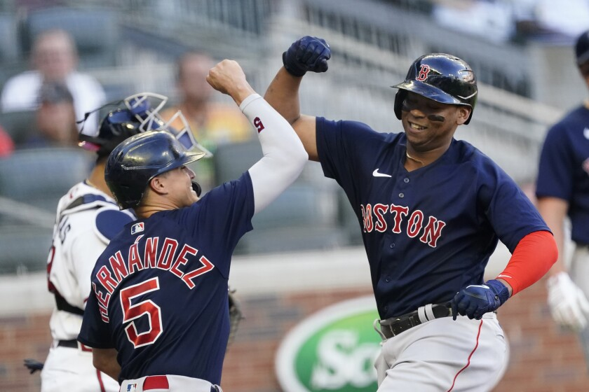 Boston Red Sox's Rafael Devers (11) celebrates with Enrique Hernandez (5) after hitting a three-run home run in the first inning of the team's baseball game against the Atlanta Braves Tuesday, June 15, 2021, in Atlanta. (AP Photo/John Bazemore)