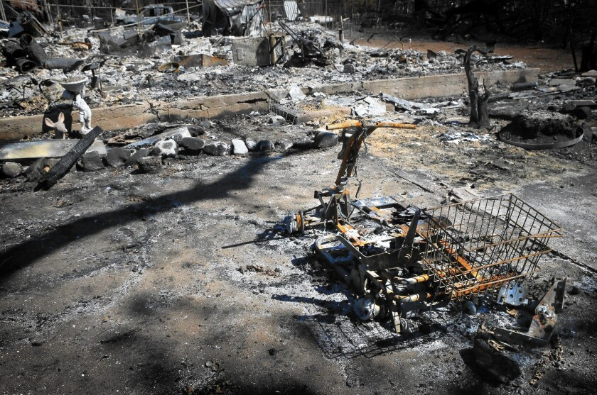 The charred remains an electric scooter sit outside a destroyed home after the Valley fire struck Middletown.