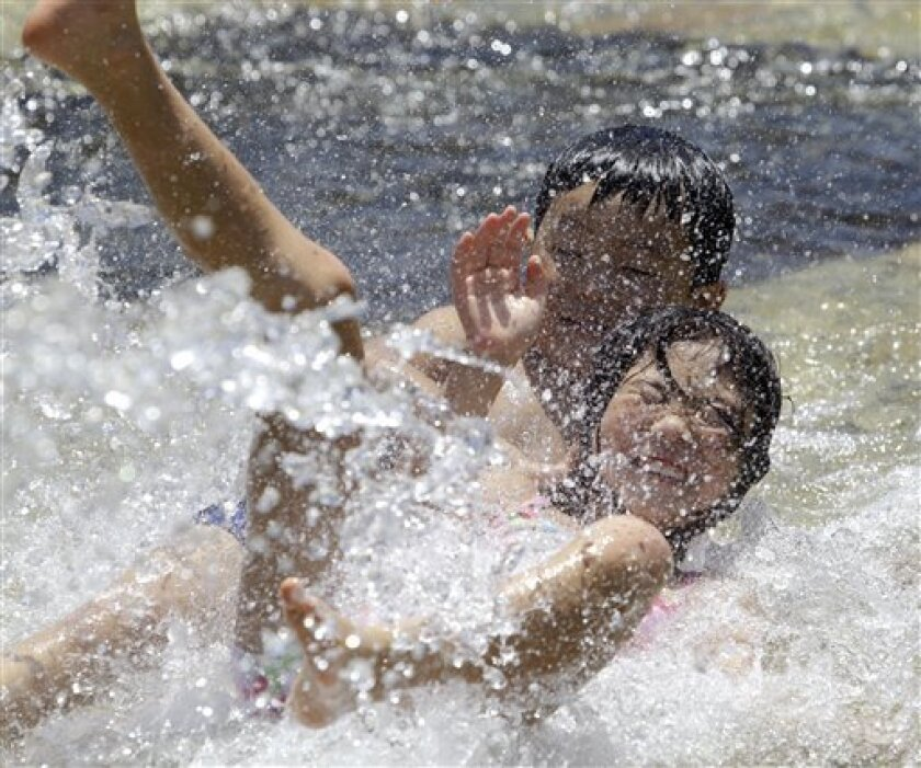 In this July 17, 2010 photo, children beat the summer heat in a fountain at a Tokyo park when the temperature in central Tokyo shot up to 31 degrees Celsius (88 F) at noon. Japan had the hottest summer on record, according to weather officials. The country's average temperature from June through August was 24.37 degrees Celsius (75.87 degrees Fahrenheit), the highest since 1898 when records began, said the Japan Meteorological Agency Monday, Sept. 1, 2010. (AP Photo/Koji Sasahara)