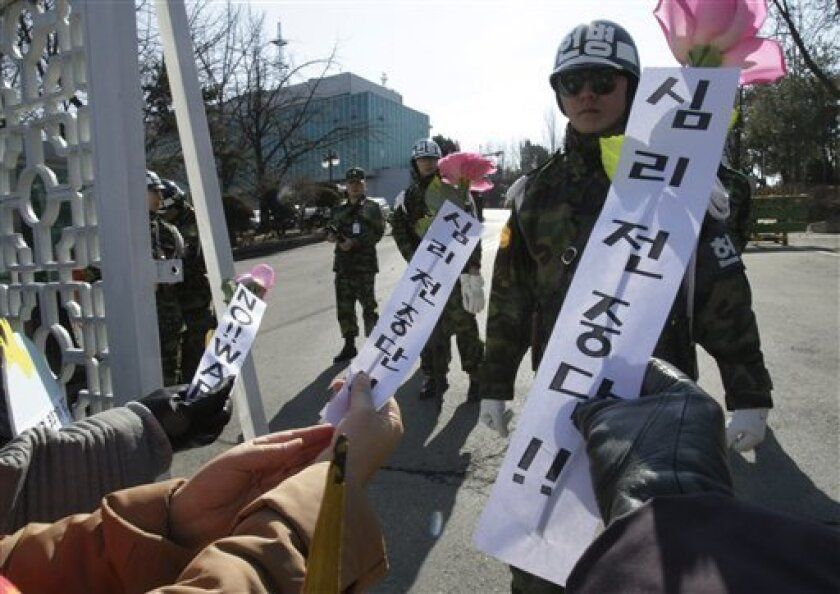 South Korean anti-war protesters try to give flowers to army soldiers during a rally against South Korean activists who  launched propaganda leaflets toward North Korea, at a main gate of Defense Ministry in Seoul, South Korea, Wednesday, March 2, 2011. South Korean activists say they will continue