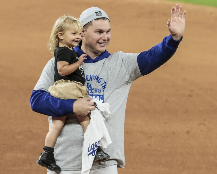 Joc Pederson and his daughter Poppy Jett celebrate on the field after the Dodges beat the Braves in Game 7.