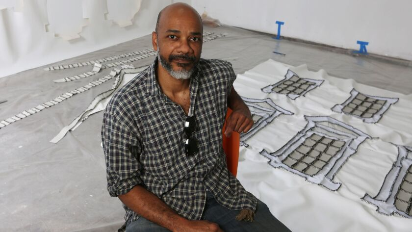 Artist Rodney McMillian sits in a chair in a studio. At his feet are pieces of white vinyl.