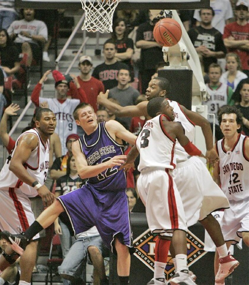 The basketball was up for grabs after Weber State's Nick Hansen had his shot blocked. (Earnie Grafton / Union-Tribune)