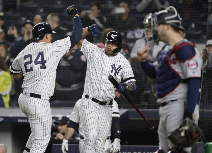 New York Yankees' Gary Sanchez, left, celebrates with teammate Gleyber Torres, center, as Minnesota Twins catcher Mitch Garver looks away during the seventh inning of a game May 3 in New York.