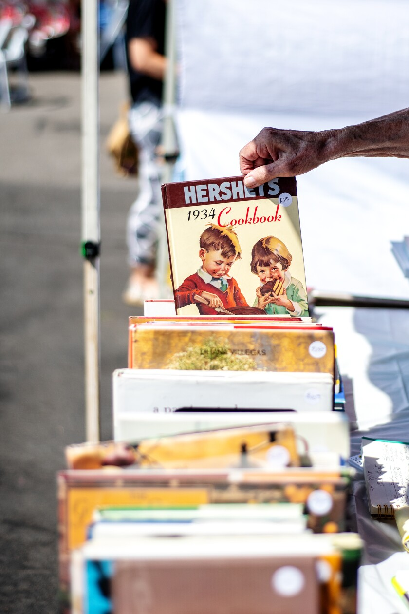 A hand pulls a 1934 Hershey's cookbook from a group of other books.