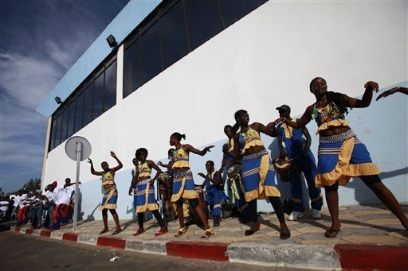 Dancers perform outside the VIP arrivals lounge as they await the arrival of a group of Haitian students, at the airport in Dakar, Senegal Wednesday, Oct. 13, 2010. Senegal is one of the poorest countries in the world and its GDP is only marginally higher than Haiti's, but that didn't stop the gove