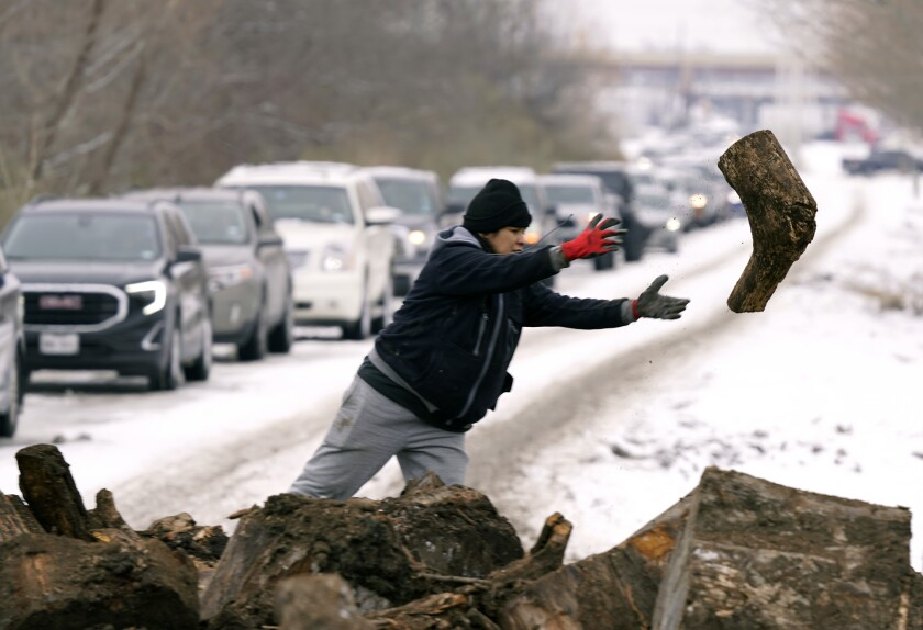 A woman tosses a log of firewood, with a long line of cars on a snowy road in the background