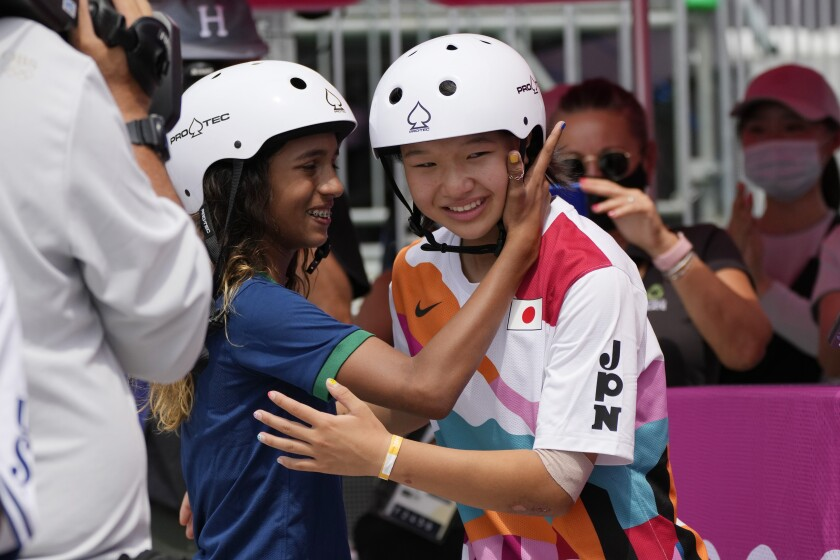Silver medalist Rayssa Leal of Brazil, left, congratulates gold medal winner Momiji Nishiya of Japan after winning the women's street skateboarding finals at the 2020 Summer Olympics, Monday, July 26, 2021, in Tokyo, Japan. (AP Photo/Ben Curtis)