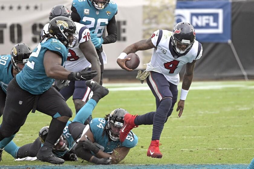 Houston Texans quarterback Deshaun Watson (4) scrambles away from Jacksonville Jaguars defensive end Dawuane Smoot (94), defensive tackle DaVon Hamilton, left, and safety Jarrod Wilson (26) during the second half of an NFL football game, Sunday, Nov. 8, 2020, in Jacksonville, Fla. (AP Photo/Phelan M. Ebenhack)