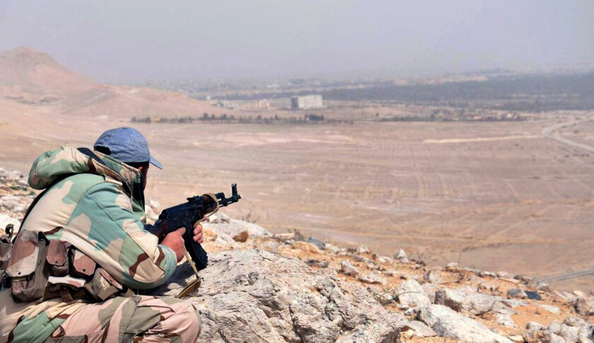 A government soldier takes position on a hill overlooking Palmyra in central Syria on Oct. 10, 2019.