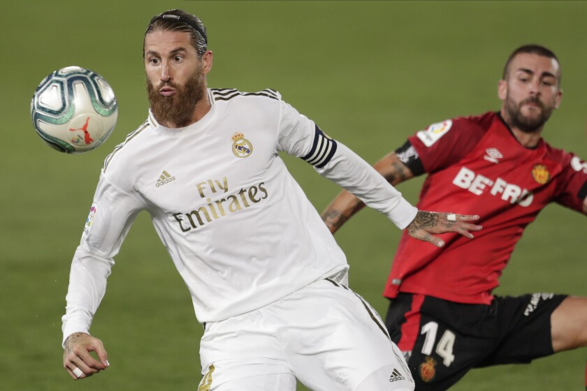 Real Madrid's Sergio Ramos fights for the ball with Mallorca's Dani Rodriguez.