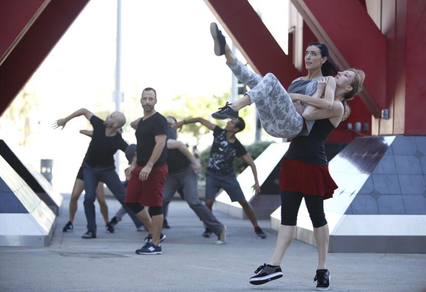Blythe Barton lifts Erica Ruse as Bradley Lundberg looks on during a presentation of Trolley Dances by San Diego Dance Theater in 2016. (Alejandro Tamayo/Union-Tribune)