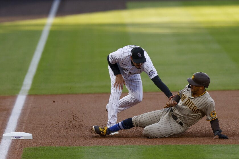 Rockies third baseman Nolan Arenado tags out Padres' Trent Grisham on Saturday at Coors Field.