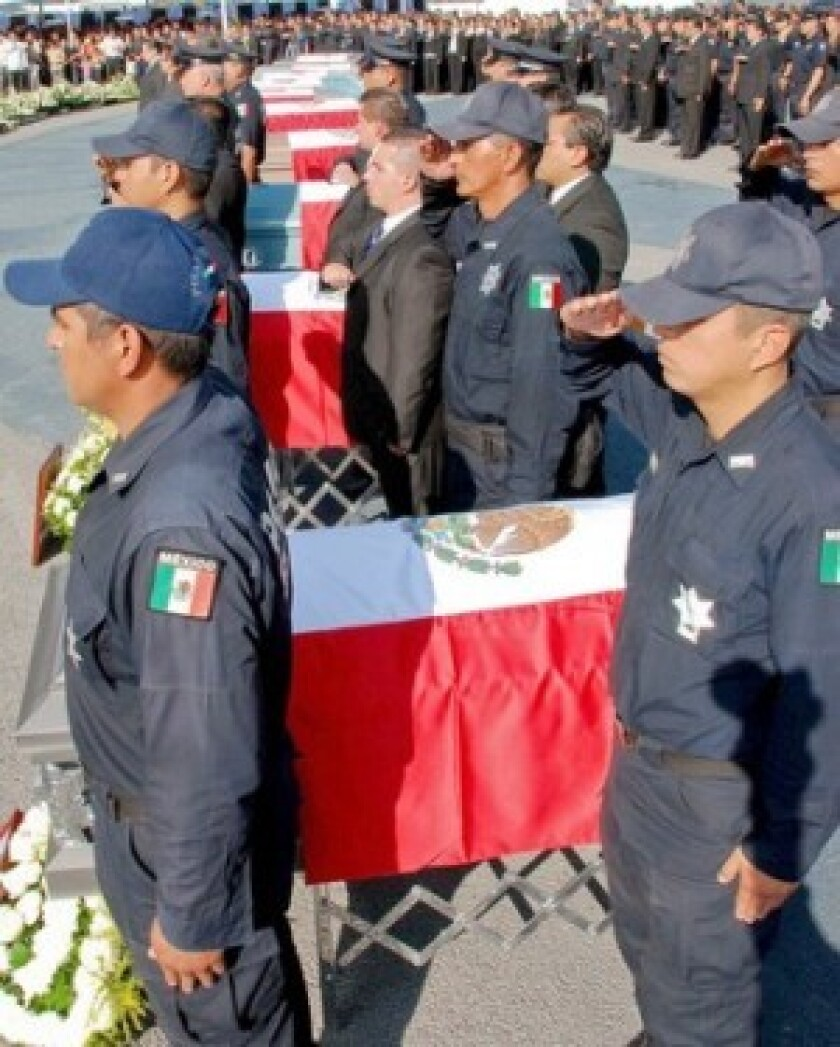 Federal police participate this week in the Mexico City funeral for 12 fellow officers whose bodies were found in a heap in the western state of Michoacan. The La Familia drug gang is suspected of killing them.