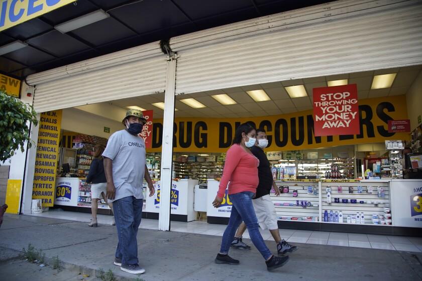 Gente camina frente a una farmacia por la Avenida de la Amistad en Tijuana