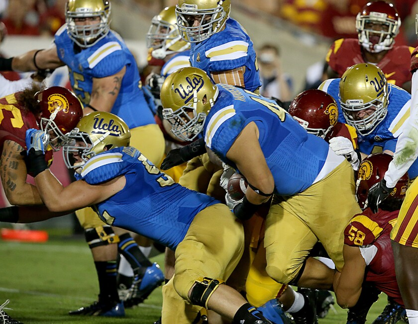 UCLA defensive tackle Eddie Vanderdoes runs the ball on offense for a touchdown against USC on Nov. 30, 2013.