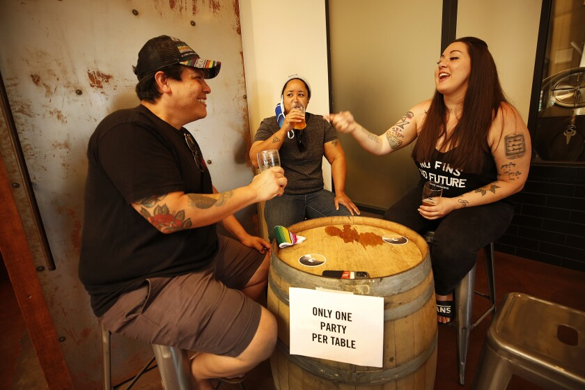 Roommates Anthony Villa, Amanda Jackson, center, and Emily Largey enjoy a beer at Ventura Coast Brewing Company in downtown Ventura after Ventura County became the largest county in Southern California to resume dine-in service.