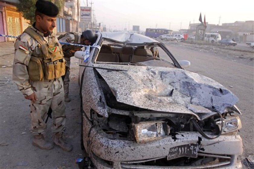 Iraqi security forces inspect a destroyed car at the scene of a car bomb attack near a popular restaurant in Basra, Iraq's second-largest city, 340 miles (550 kilometers) southeast of Baghdad, Iraq, Tuesday, Nov. 9, 2010. Car bombs struck three Shiite cities in southern Iraq on Monday, killing and wounding scores of people, police said. (AP Photo/Nabil al-Jurani)
