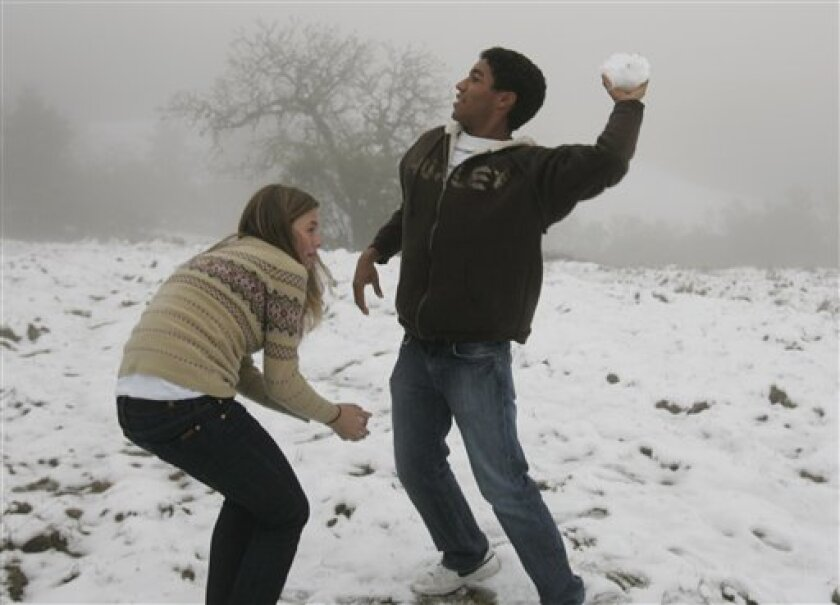 Alex Freeman, right, throws a snowball as Maya Lloyd, left, looks on in Palo Alto, Calif. on Tuesday, Dec. 16, 2008 after a snow storm in the hills. (AP Photo)