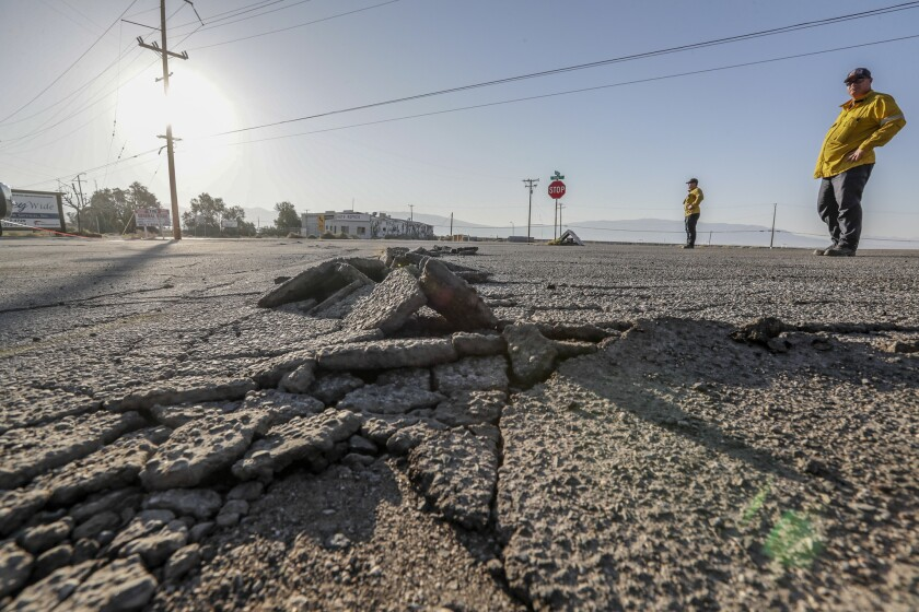 Buckled asphalt, in a parking lot near Trona Road in Argus, Calif., is evidence of recent quakes.