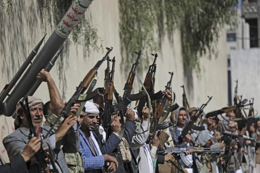 Yemeni tribesmen loyal to the Houthi rebel movement raise their weapons