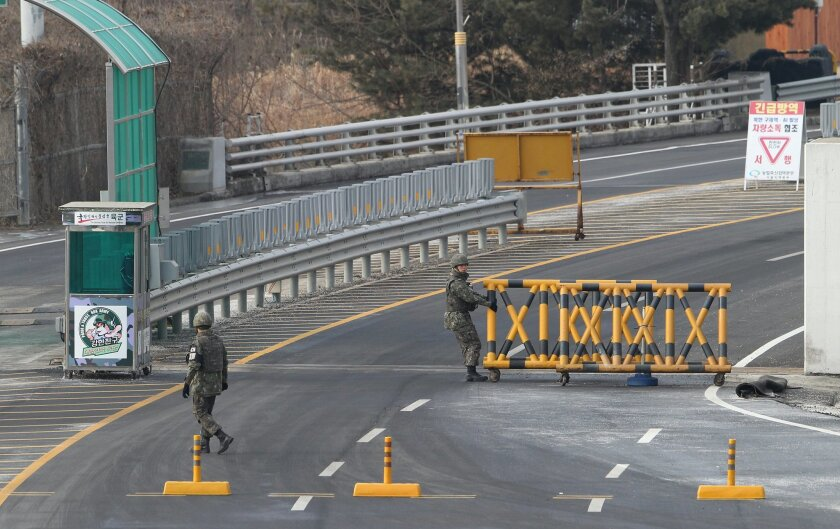 In this Feb. 11, 2016, photo, a South Korean army soldier moves a barricade to close a road at the customs, immigration and quarantine office near the border village of Panmunjom, in Paju, South Korea. Furious about North Korea's recent nuclear test and long-range rocket launch, South Korea vows to