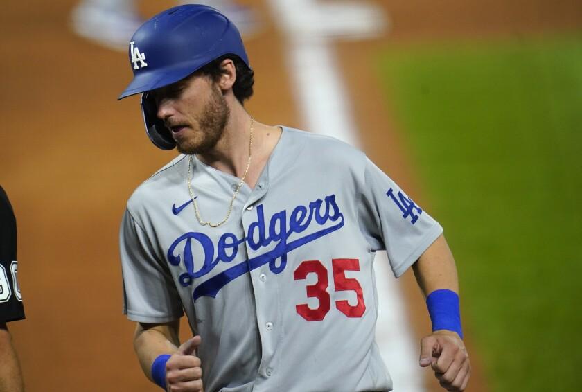 Cody Bellinger, de los Dodgers de Los Ángeles, anota en un sencillo del puertorriqueño Edwin Ríos en el duelo del viernes 18 de septiembre de 2020, ante los Rockies de Colorado (AP Foto/David Zalubowski)