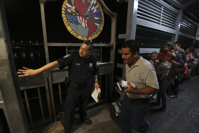 n agente de la Patrulla Fronteriza señala a dónde ir a una familia migrante nicaragüense