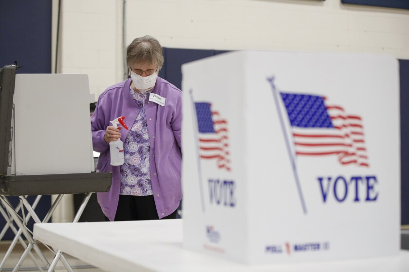 An election worker cleans voting booths Tuesday at the Kenosha Bible Church gym.