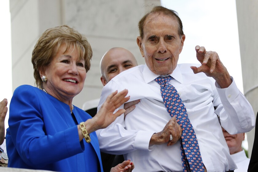 """FILE - In this May 27, 2019 file photo, former Sen. Bob Dole, right, and his wife Elizabeth Dole acknowledge well-wishers during a Memorial Day ceremony, at Arlington National Cemetery in Arlington, Va. The political icon and 1996 Republican presidential nominee on Monday, Jan. 13, 2020, endorsed western Kansas' congressman Rep. Roger Marshall in the state's GOP Senate primary. Marshall's campaign announced Dole's backing and Dole tweeted that Marshall is """"a true friend to KS."""" Marshall has served in Congress since 2017. (AP Photo/Patrick Semansky File)"""