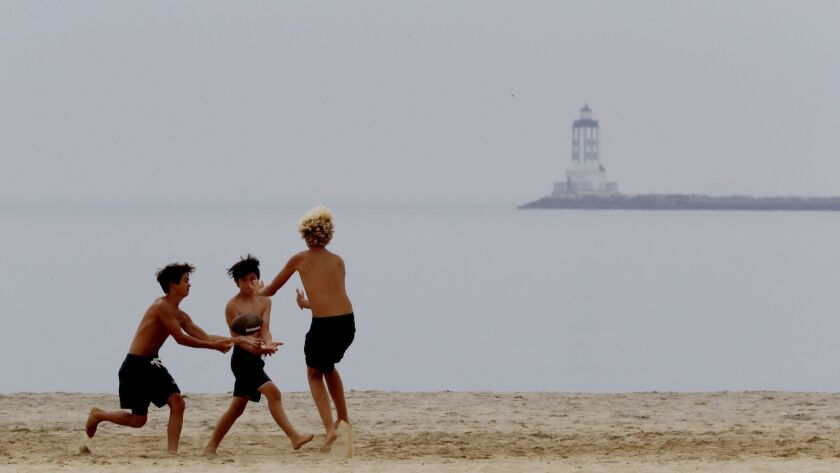 SAN PEDRO, CALIF. - JULY 18, 2018. A pall of gray clouds hangs over junior lifeguards playing footb