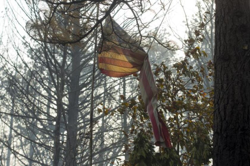 A singed US flag blows in the wind at a burned down Magalia home after the Camp Fire burned through the region, fueled by high winds in Butte County, California, USA, 11 November 2018. The nearby communities of Pulga, Paradise and Concow, have been ordered to evacuate the area. EPA-EFE/FILE/PETER DASILVA