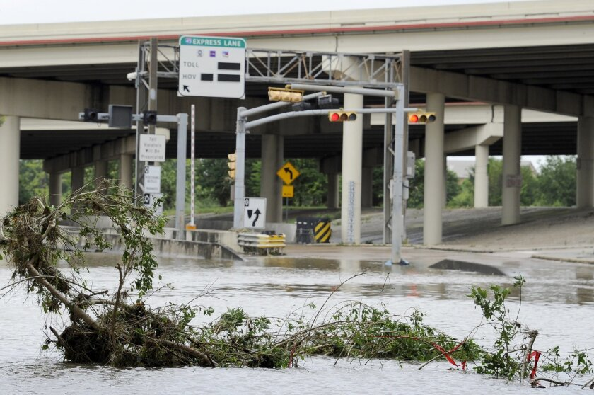 A highway entrance is covered in water and debris after flood waters overran the banks of the bayou in downtown Houston, Tuesday, May 26, 2015. Floodwaters kept rising Tuesday across much of Texas as storms dumped almost another foot of rain on the Houston area, stranding hundreds of motorists and