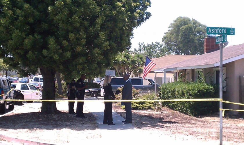 Officers stand in front of the house on Ashford Street where a body was found earlier this morning.